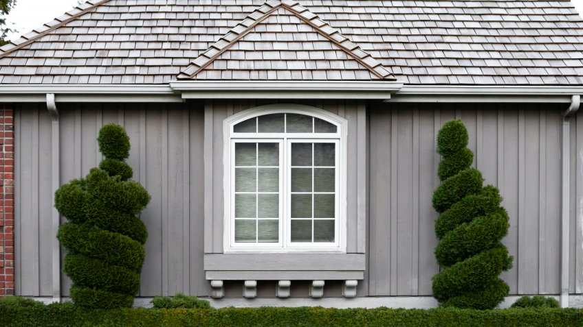 Centered view on the exterior of a craftsmen style home framed by spiral bushes, in a residential architectural background - Image.