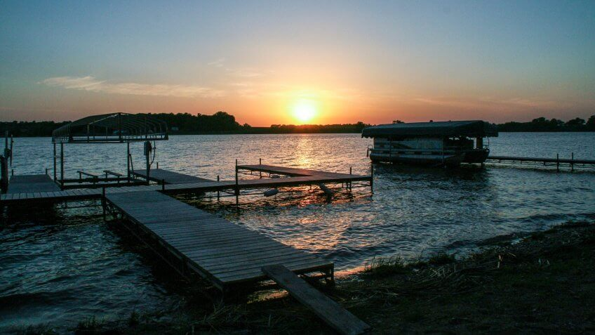 Sunset on a dock with pontoon boat on Lake Reno in Alexandria, Minnesota - Image.