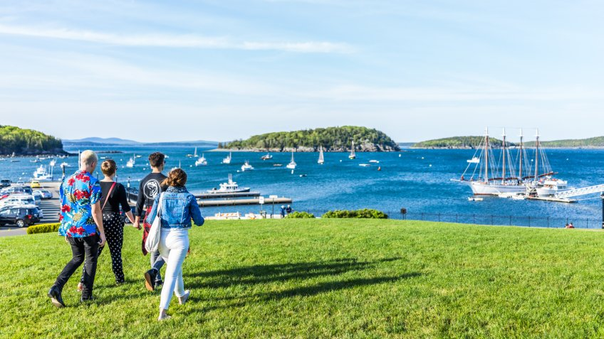 Bar Harbor: Group of young people walking on green grass hill in park downtown village in summer by boats.