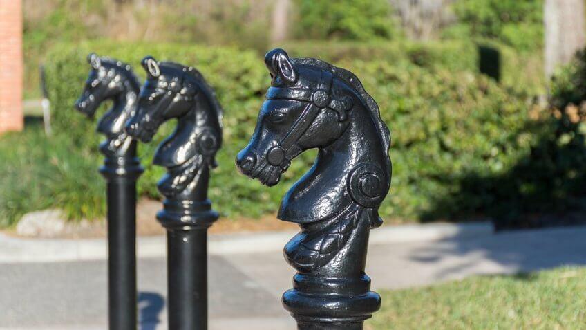 Black painted bollard   shaped as a horse head.