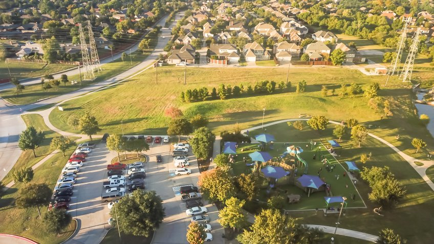 Top view playground near residential neighborhood with overhead power lines in Carrollton, suburbs Dallas, Texas, USA.