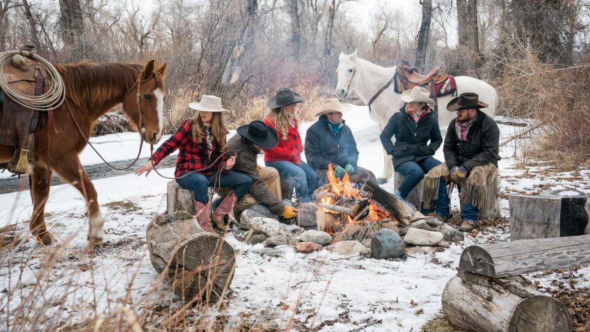 Three Caucasian couples in their 20's huddle around a campfire outdoors with two horses on a winter day, Livingston, Montana, USA.