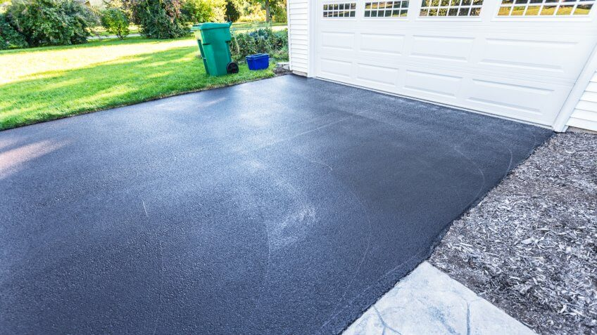 A fresh blacktop resealing job just finished on this asphalt driveway in a suburban residential district.
