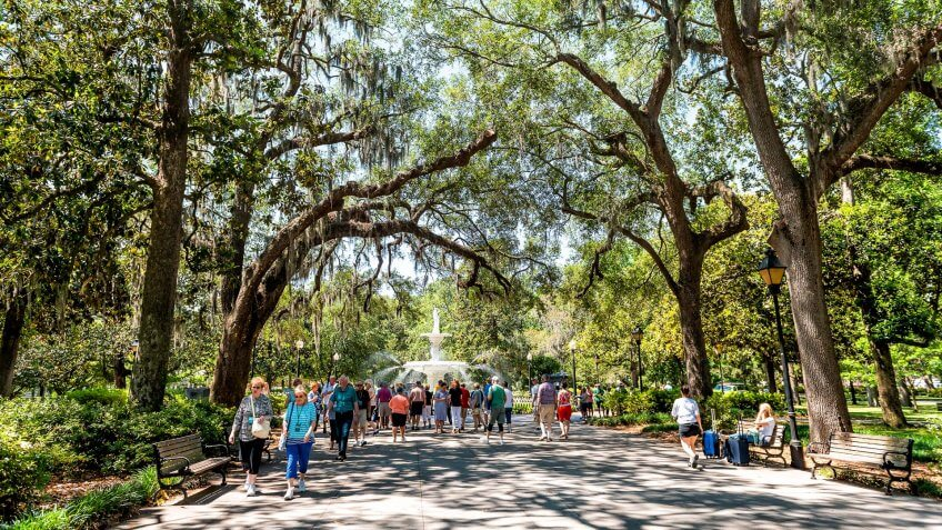 Savannah, USA - May 11, 2018: Famous water fountain in Forsyth park, Georgia during sunny day in summer with people walking on alley street.