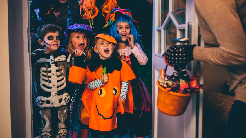 Group of children and their parents playing trick or treat on Halloween.