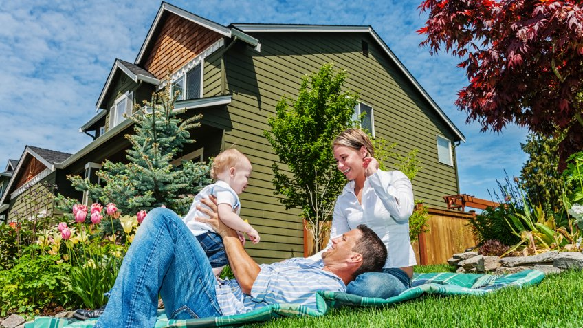 Photo of a happy family in front of their home, enjoying a sunny day in the yard on a blanket.