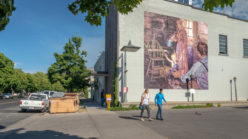Logan, Utah, United States - August 31, 2018: Mural showing a traditional family with a couple passing by in the foreground taken in Logan, Utah.