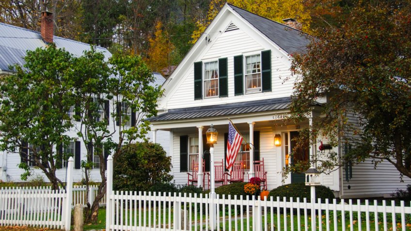 White clapboard house with a white picket fence.