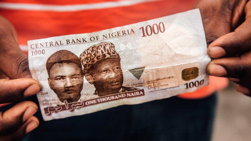 African man holding money - Nigerian Naira.