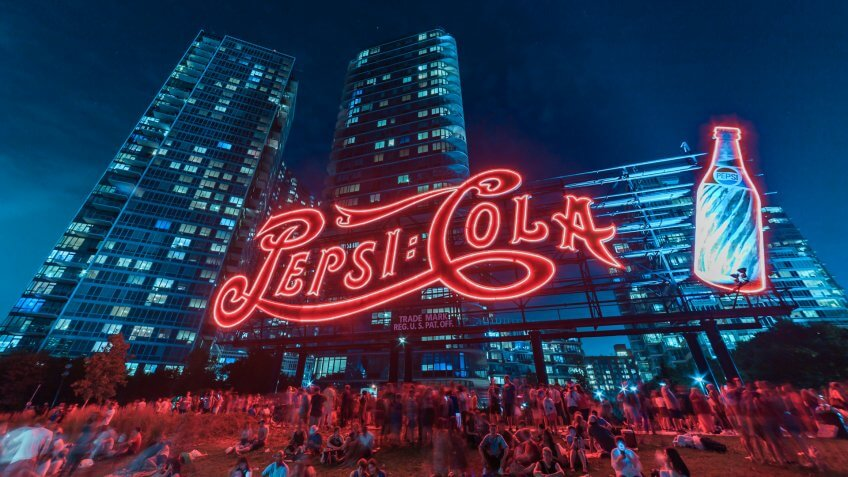 Image shows the Pepsi Cola sign and many people sitting on the ground during the celebration of the Independence day at night.