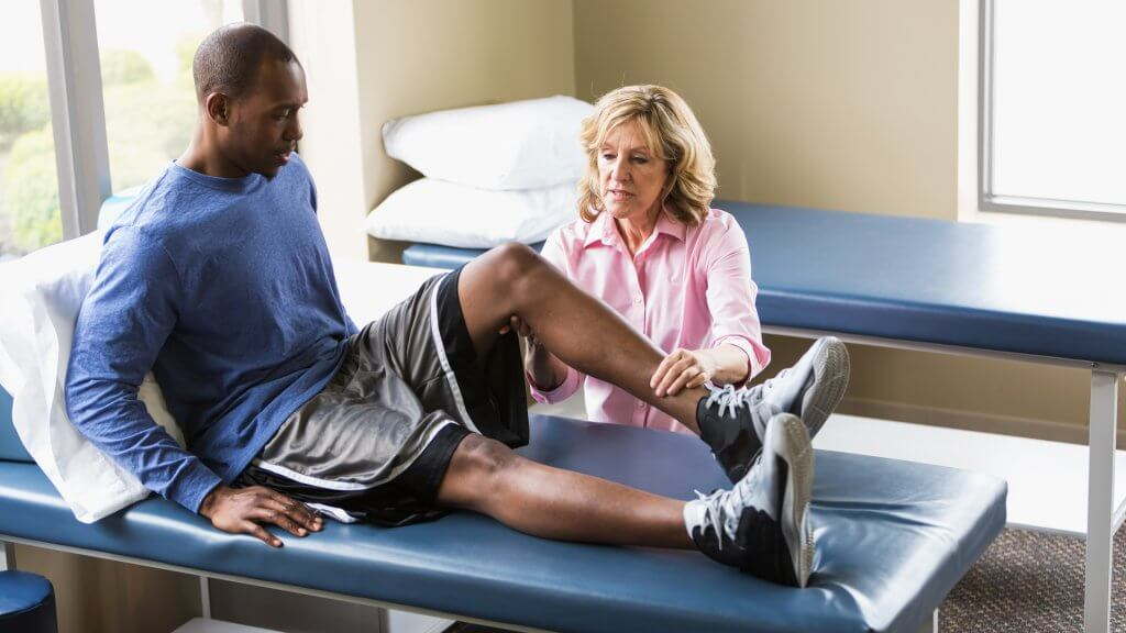 A female physical therapist examining a young African American man on a treatment table.