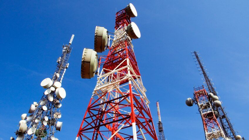 Telecommunications towers on blue sky, a red and white, the other white, antennas for television, radio, and mobile phones.