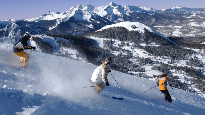 Skiers on Telluride's Gold Hill with the majestic Wilson Massif in the background.