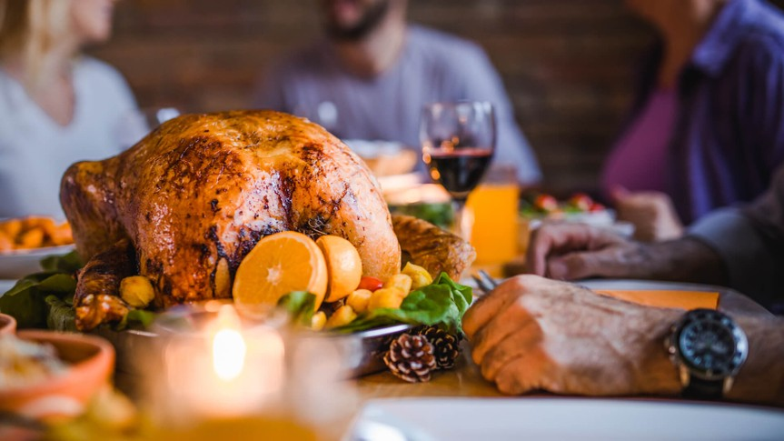 Close up of stuffed roasted turkey during family's dinner at dining table.