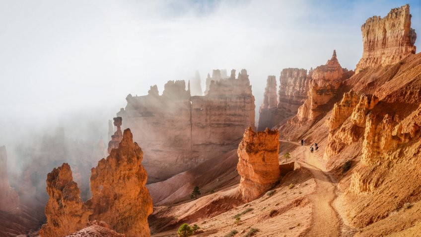 People trekking the Navajo loop trail in Bryce Canyon National Park at sunrise with some clouds and fog.