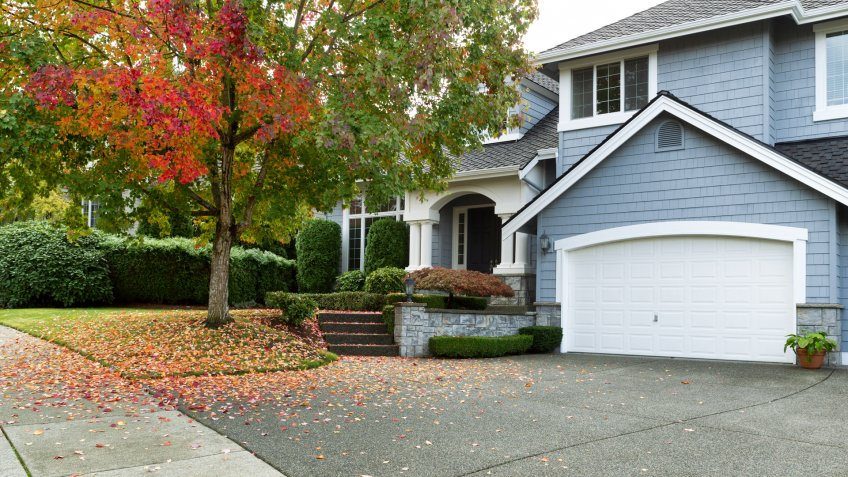 Driveway to front walkway view of partial front of residential home during early autumn season.