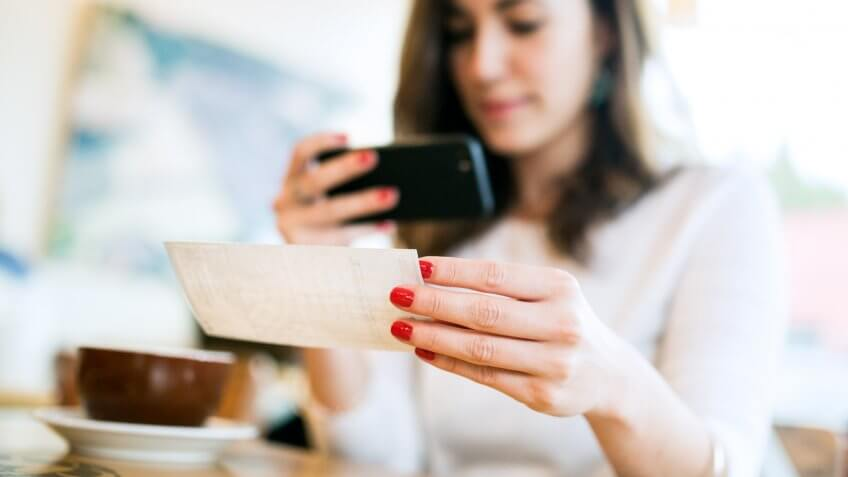 """A smiling young woman takes a picture with her smart phone of a check or paycheck for digital electronic depositing, also known as """"Remote Deposit Capture""""."""