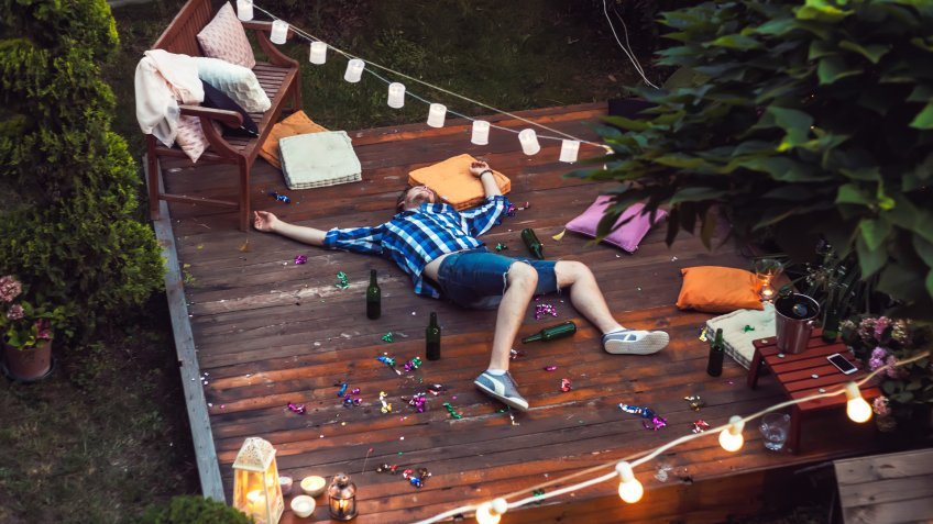 Young man sleeping after party in a backyard.