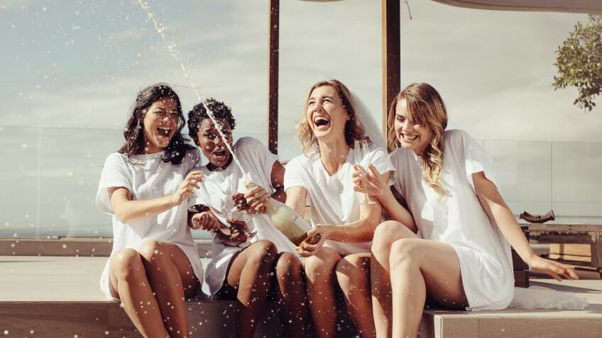 Cheerful bride and bridesmaids celebrating hen party with champagne while sitting on rooftop.
