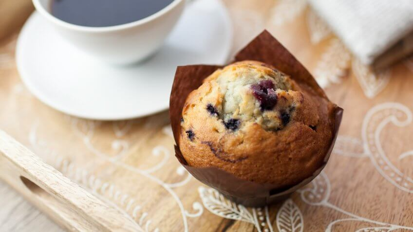 Black coffee in a cup and saucer with a blueberry muffin on a wooden tray with newspaper.