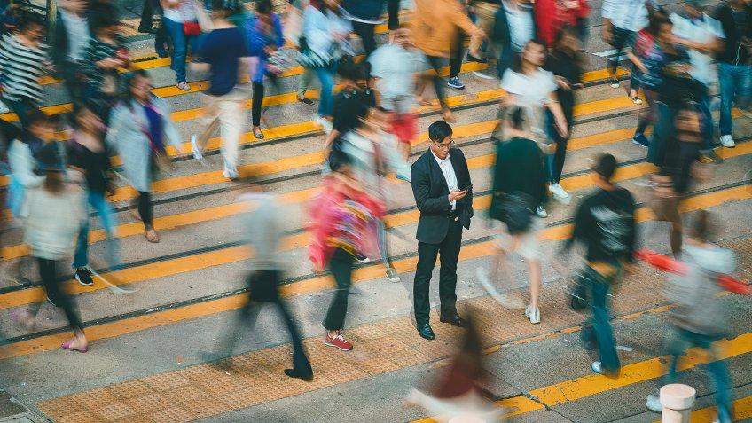 businessman standing in busy pedestrian crosswalk