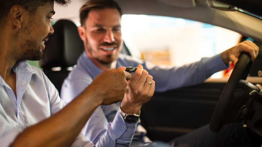 Car salesman giving the car keys to a potential buyer for a test drive as they sit together in a new model of a car in an automobile dealer salon.