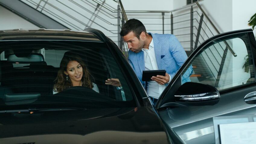 Vehicle dealer showing young woman new car.