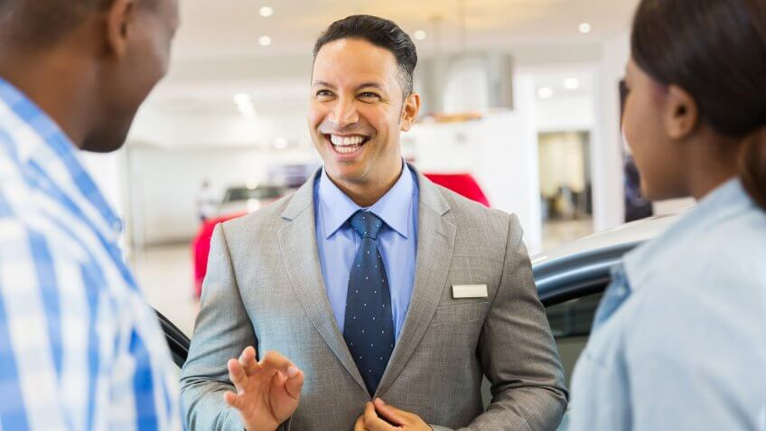 handsome vehicle dealer talking to customers in showroom.