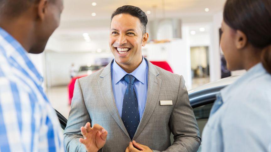 handsome vehicle dealer talking to customers in showroom.