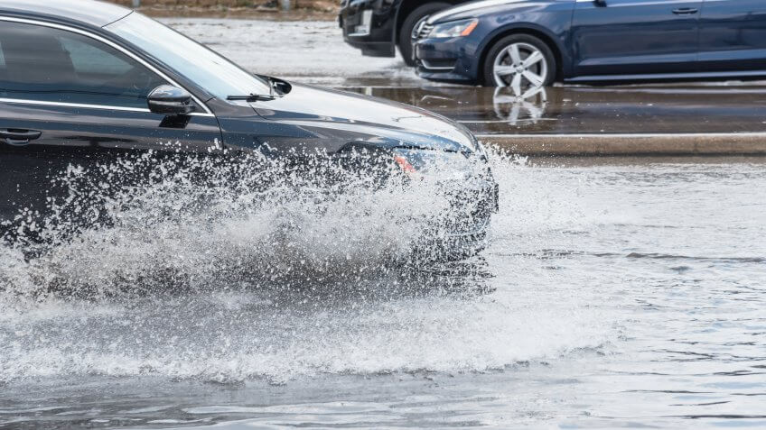 cars driving through flooded street