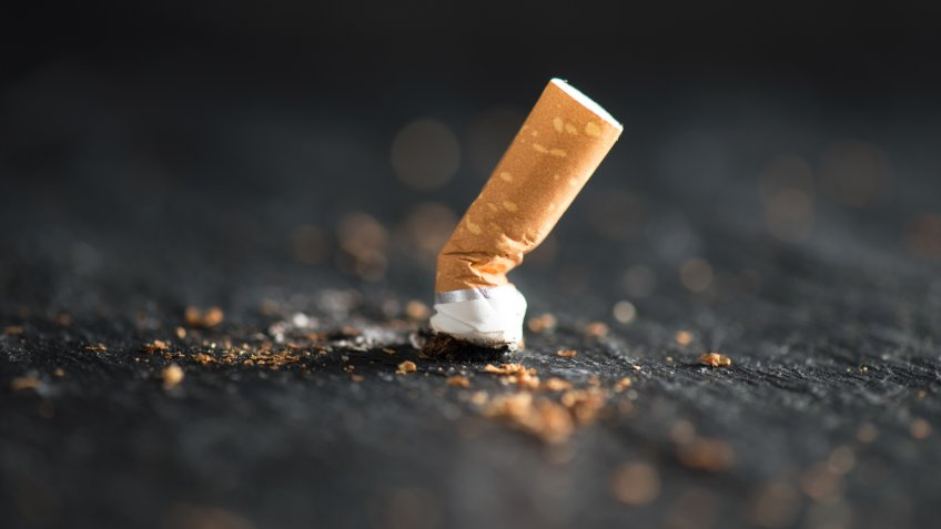 Cigarette butt on abstract background.