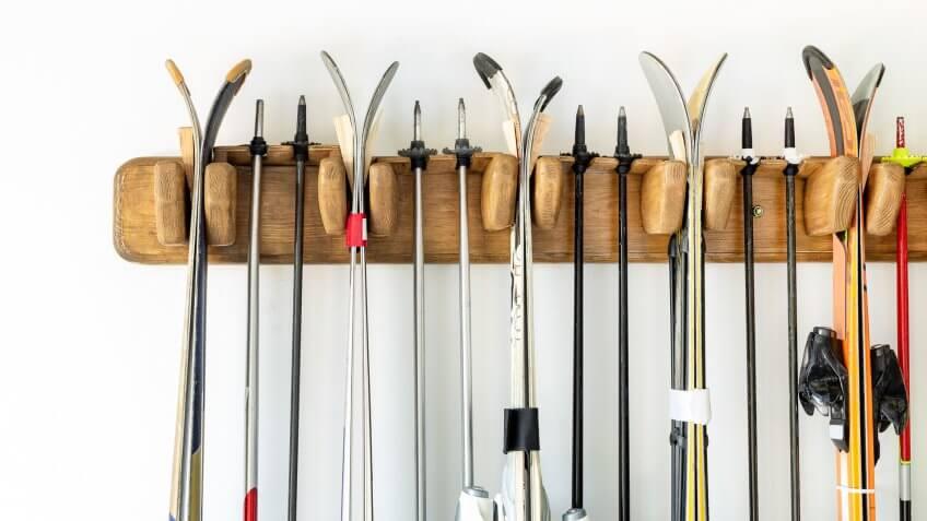 Lot of ski hanged on customized wooden wall mount at garage for seasonal storage.