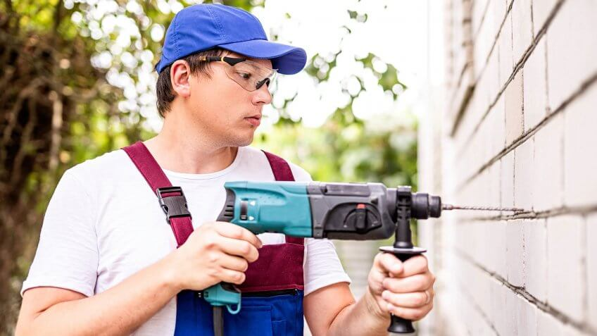 Building worker in in protection glasses and uniform with perforator drilling the wall outdoors.