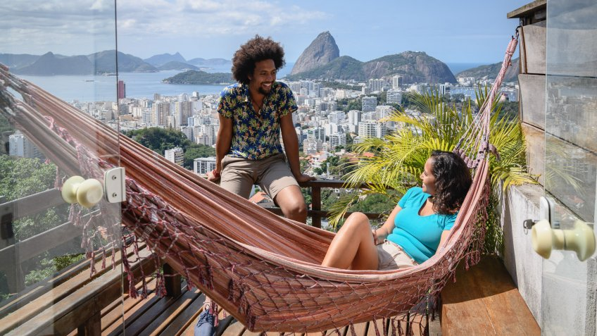 Brazilian couple smiling at each other on decking, woman in hammock, Sugar Loaf Mountain in the distance.