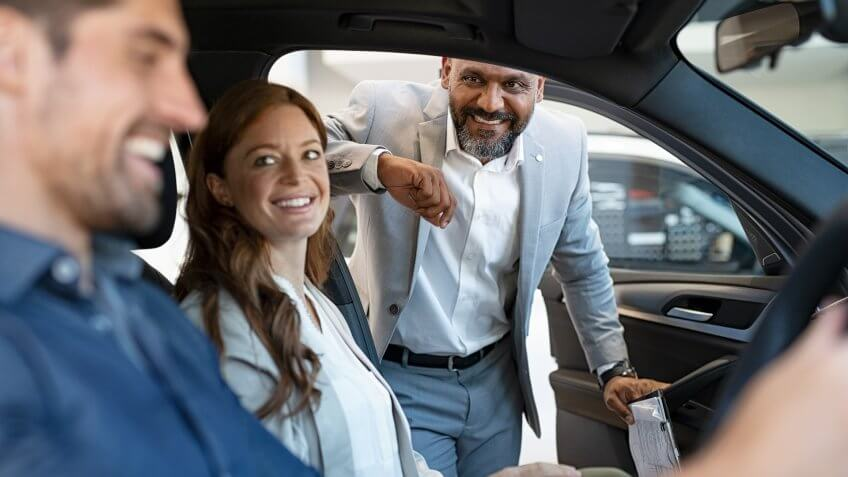 African salesman showing new car to young couple in showroom.