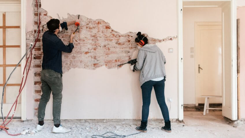 Young couple working on reconstruction of their apartment.