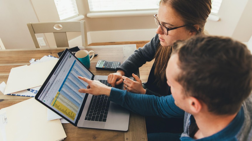 A young millennial married couple are doing their monthly budget at a kitchen dining room table in their home.