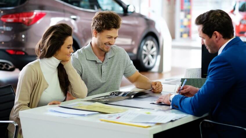 couple signing loan on their new used car
