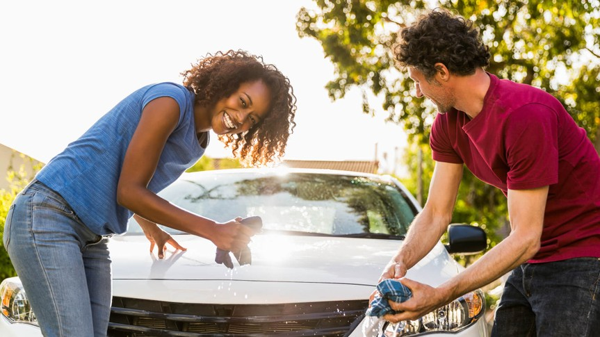 Portrait of cheerful woman cleaning car with man at yard.