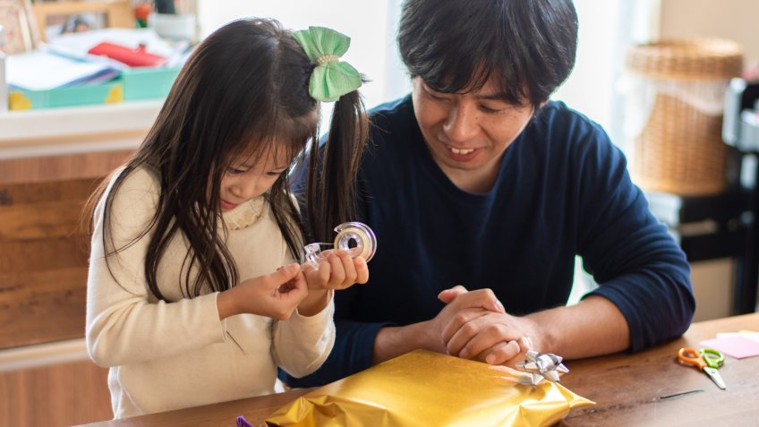 A candid front view photo of a Japanese father wrapping Christmas presents with his daughter.