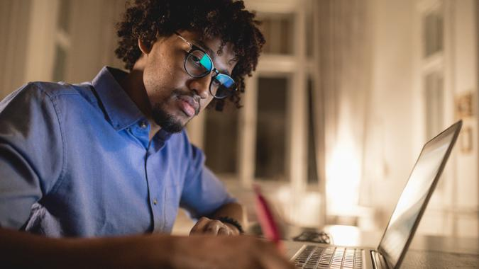 Young and determined black student studying at night at home, with a help of a laptop computer.