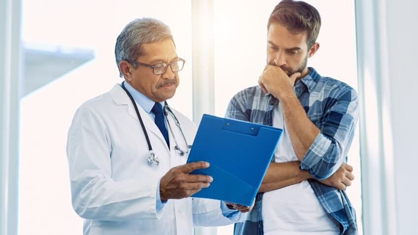 Shot of a confident mature male doctor showing test results to a patient inside of a hospital during the day.