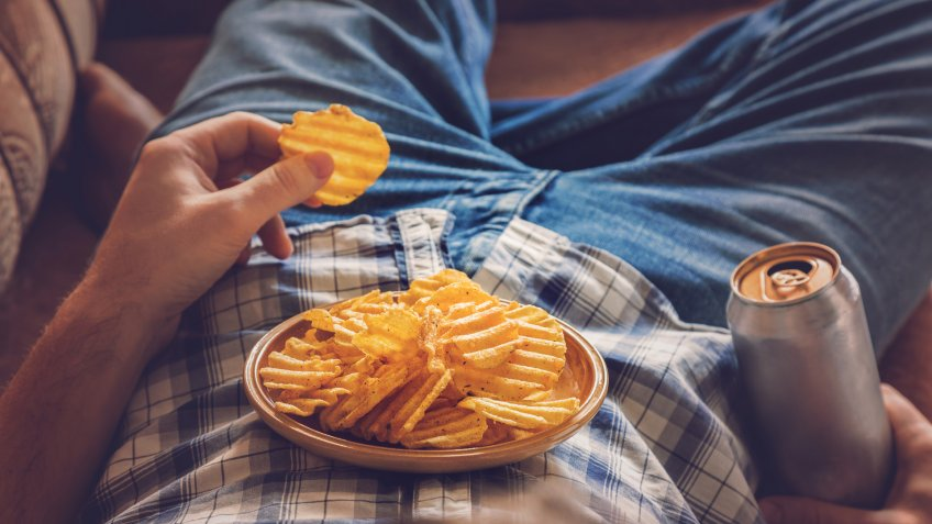 eating chips and junk food on the couch