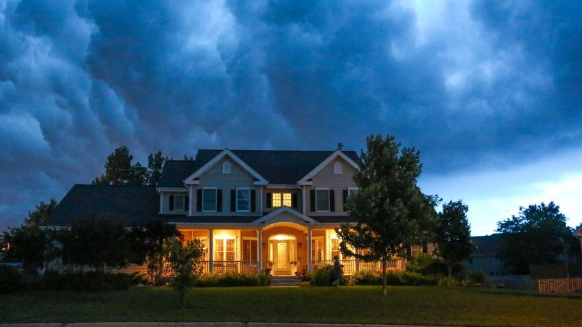 A well appointed house is lit up while a large thunderstorm moves in overhead.