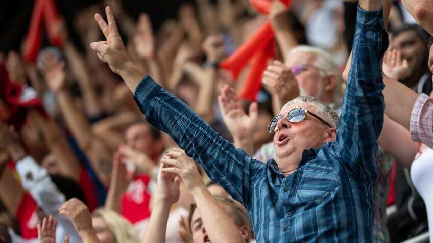 Portrait of a middle-aged man with sunglasses raising his arms in reaction to his team winning.