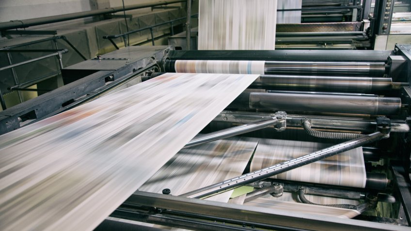 Newspapers being printed in printing press.