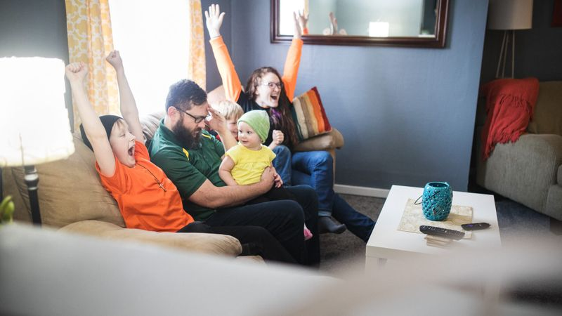 A happy family with three children have fun goofing off while watching a sports game on the television.