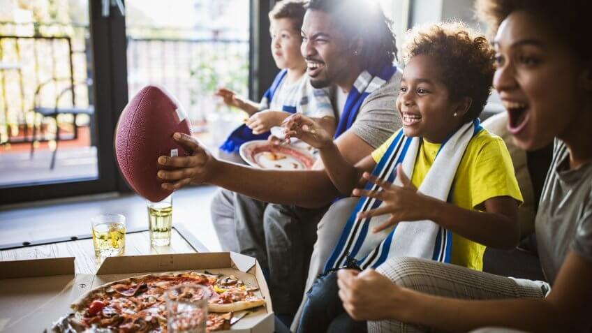 Young joyful black family having fun while cheering for their favorite American football team at home.