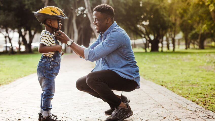 African man putting helmet on cute boy at the park.