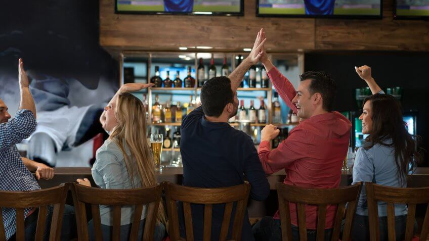 Happy group of friends watching sports at the bar and drinking beer.